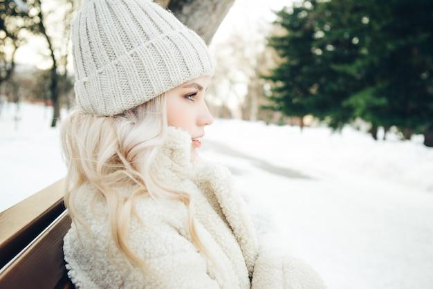 Jovem loira bonita senta-se em um banco no parque no inverno