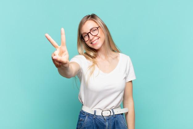 Jovem loira bonita sorrindo e parecendo amigável, mostrando o número dois ou o segundo com a mão para a frente, em contagem regressiva