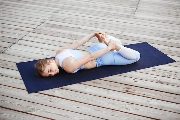 Jovem loira bonita sorrindo, praticando ioga fora.