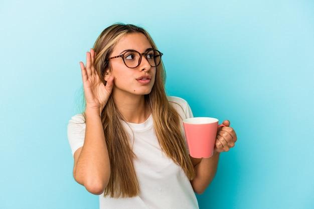 Jovem loira branca segurando uma caneca isolada na parede azul tentando ouvir uma fofoca