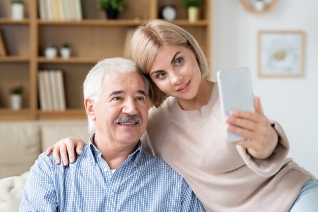 Jovem loira carinhosa abraçando o pai idoso enquanto relaxa em casa e faz selfie