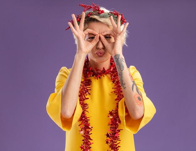 Jovem loira carrancuda usando coroa de natal na cabeça e guirlanda de ouropel em volta do pescoço olhando fazendo gesto de olhar usando as mãos como binóculos com lábios franzidos, isolados na parede roxa com espaço de cópia