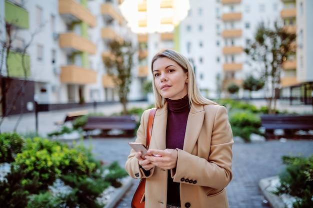 Jovem loira caucasiana atraente no casaco e com bolsa em pé no parque, olhando alguma coisa e segurando o telefone inteligente nas mãos.