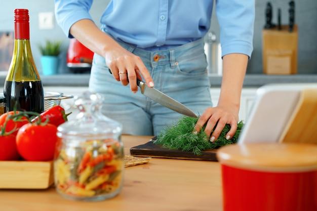 Jovem loira caucasiana cortando vegetais para salada na cozinha
