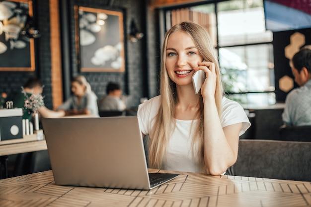 Jovem loira caucasiana freelancer em um café com telefone e laptop