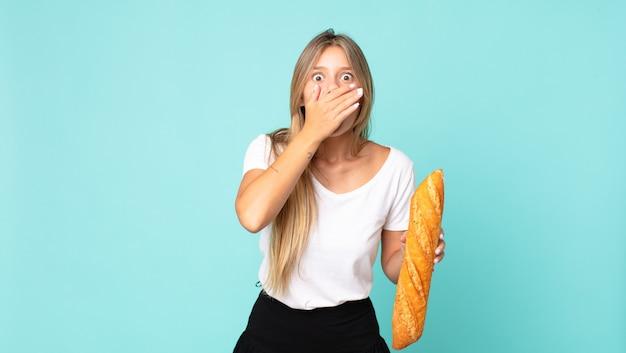 Jovem loira cobrindo a boca com as mãos em choque e segurando uma baguete de pão