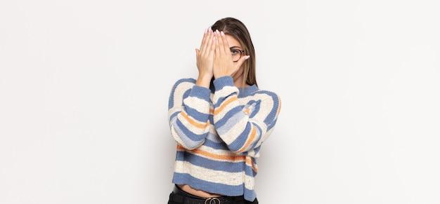 Jovem loira cobrindo o rosto com as mãos, espiando por entre os dedos