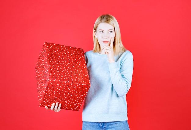Jovem loira colocando a mão perto do rosto enquanto segura a caixa de presente vermelha