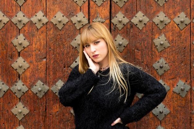 Jovem loira com cabelo comprido, posando em uma porta de madeira antiga.