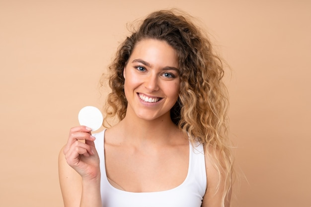 Jovem loira com cabelo encaracolado isolado em uma parede bege com almofada de algodão para remover a maquiagem do rosto e sorrindo