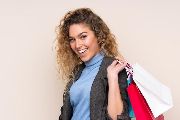 Jovem loira com cabelo encaracolado isolado em uma parede bege segurando sacolas de compras e olhando para trás