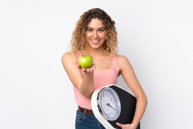 Jovem loira com cabelo encaracolado isolado na parede branca segurando uma máquina de pesar e oferecendo uma maçã