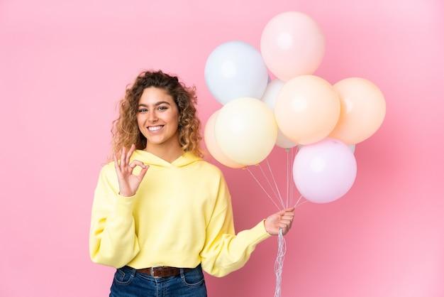 Jovem loira com cabelo encaracolado pegando muitos balões isolados na rosa e mostrando um sinal de ok com os dedos