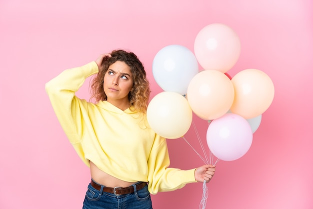 Jovem loira com cabelos cacheados pegando muitos balões isolados na rosa tendo dúvidas e com expressão facial confusa