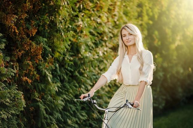 Jovem loira com cabelos longos em pé perto de bicicleta branca vintage.