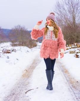 Jovem loira com casaco de pele rosa e chapéu roxo na neve. caminhando em um caminho cheio de neve, estilo de vida de inverno