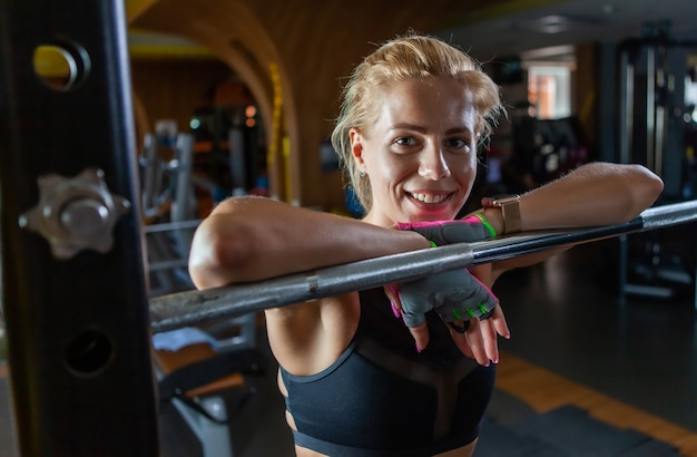 Jovem loira com corpo perfeito, descansando após exercícios de agachamento no ginásio.