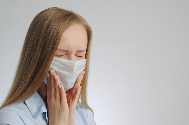 Jovem loira com dor de dente e máscara médica