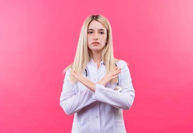 Jovem loira com estetoscópio e vestido de médico, mostrando o gesto de não na parede rosa isolada