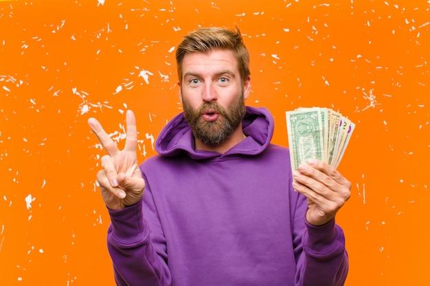 Jovem loira com notas de dólar ou notas vestindo um capuz roxo contra parede laranja danificada
