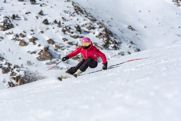 Jovem loira com óculos de esqui e capacete esquiando em uma encosta de montanha nevada