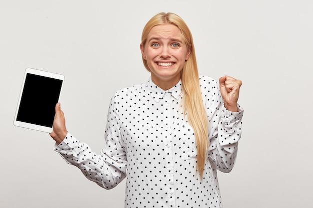 Jovem loira com os punhos cerrados de alegria, parece feliz com o tablet na mão