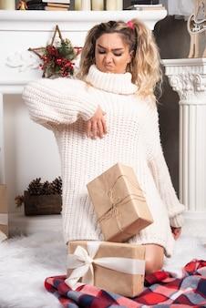 Jovem loira com presentes, olhando para seu suéter.