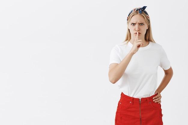 Jovem loira com raiva e incomodada posando contra a parede branca
