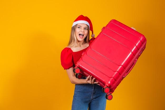 Jovem loira com roupa de natal e mala de viagem. conceito de viagem de natal