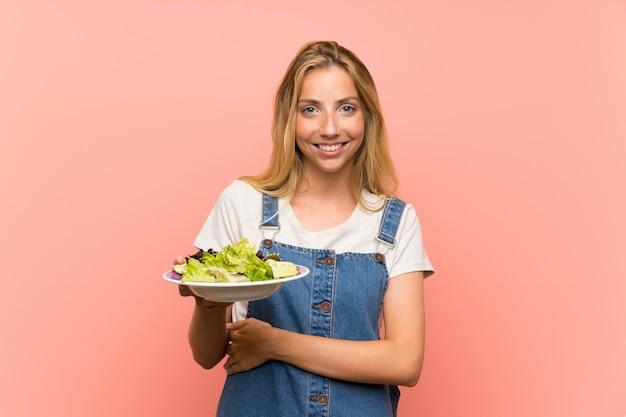 Jovem loira com salada sobre parede rosa isolada, olhando para cima enquanto sorrindo