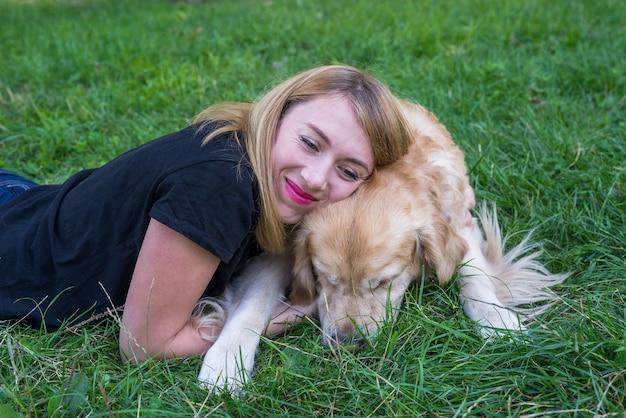 Jovem loira com seu cachorro retriever no parque