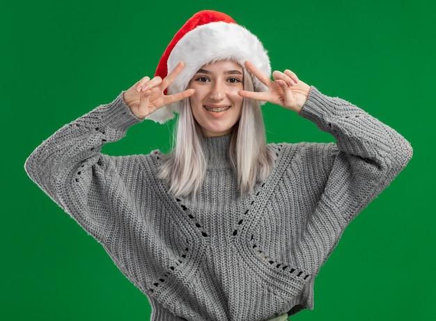 Jovem loira com suéter de inverno e chapéu de papai noel olhando para a câmera e sorrindo alegremente mostrando o sinal v em pé sobre um fundo verde