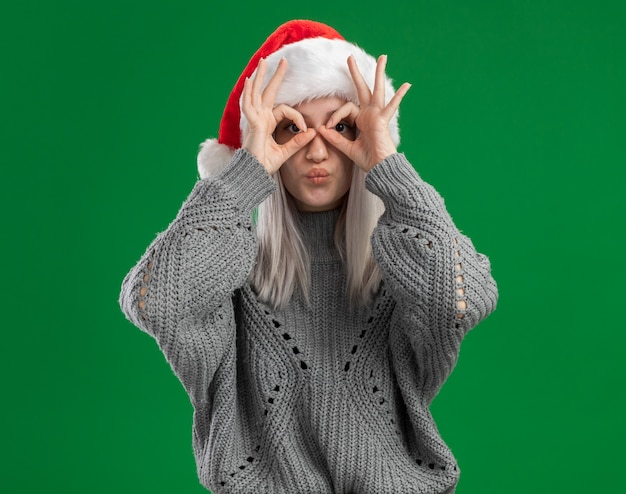Jovem loira com suéter de inverno e chapéu de papai noel olhando por entre os dedos fazendo um gesto binocular feliz e positivo em pé sobre um fundo verde