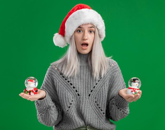 Jovem loira com suéter de inverno e chapéu de papai noel segurando globos de neve de brinquedo de natal, olhando para a câmera espantada e surpresa em pé sobre fundo verde