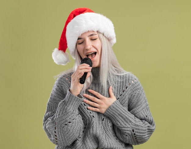 Jovem loira com suéter de inverno e chapéu de papai noel segurando o microfone cantando com os olhos fechados, feliz e positiva