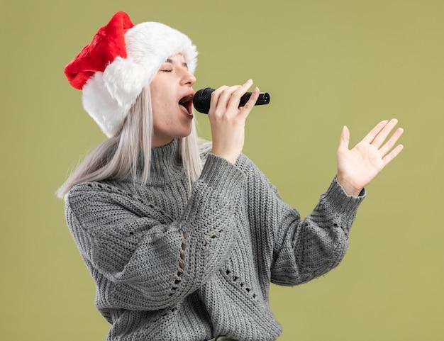 Jovem loira com suéter de inverno e chapéu de papai noel segurando o microfone cantando feliz e positiva, comemorando a festa de natal