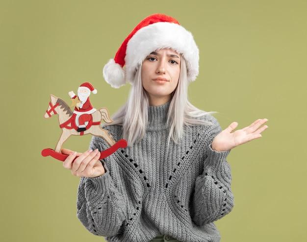Jovem loira com suéter de inverno e chapéu de papai noel segurando um brinquedo de natal, confusa e desagradável com o braço levantado em pé sobre a parede verde