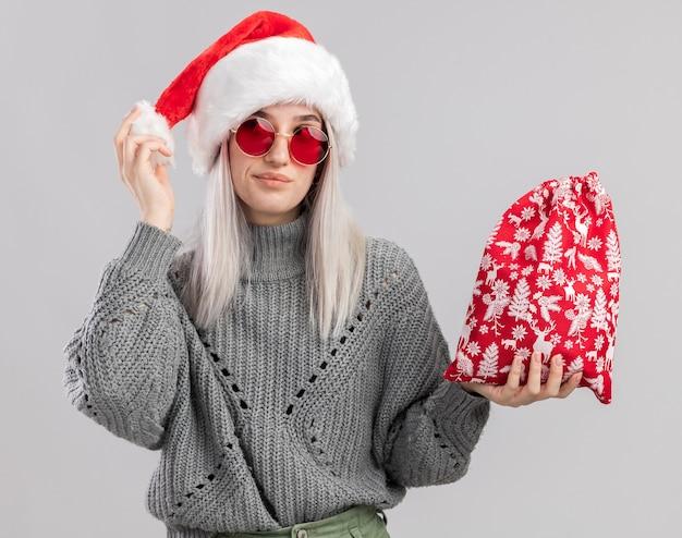 Jovem loira com suéter de inverno e chapéu de papai noel segurando uma sacola vermelha de papai noel com presentes de natal feliz e alegre olhando de lado em pé sobre uma parede branca