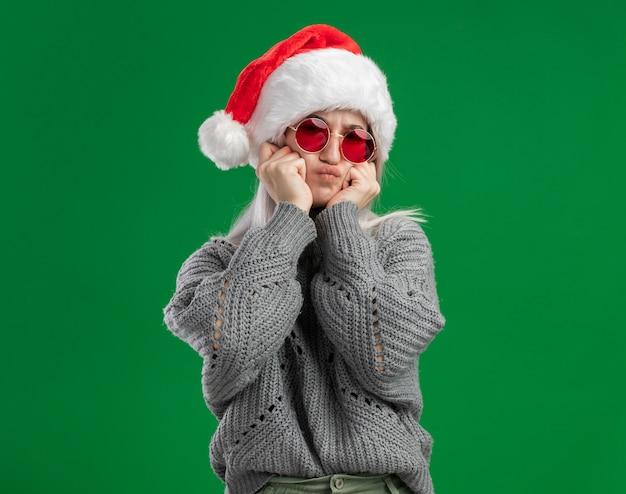 Jovem loira com suéter de inverno e chapéu de papai noel usando óculos vermelhos, olhando para a câmera, fazendo careta e se divertindo em pé sobre um fundo verde