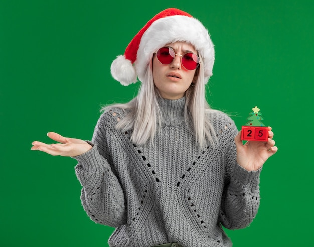 Jovem loira com suéter de inverno e chapéu de papai noel usando óculos vermelhos segurando cubos de brinquedo com data de natal e parecendo confusa com o braço estendido sobre um fundo verde