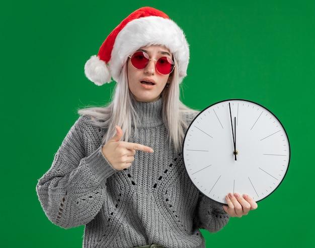 Jovem loira com suéter de inverno e chapéu de papai noel usando óculos vermelhos segurando um relógio de parede apontando com o dedo indicador para ele, parecendo confusa em pé sobre um fundo verde