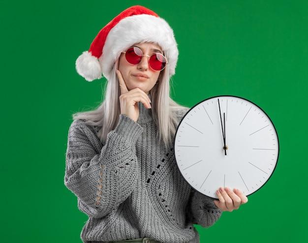 Jovem loira com suéter de inverno e chapéu de papai noel usando óculos vermelhos segurando um relógio de parede com expressão pensativa pensando em pé sobre a parede verde