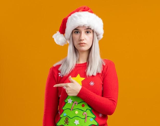 Jovem loira com suéter de natal e chapéu de papai noel com cara séria apontando com o dedo indicador para o lado em pé sobre uma parede laranja