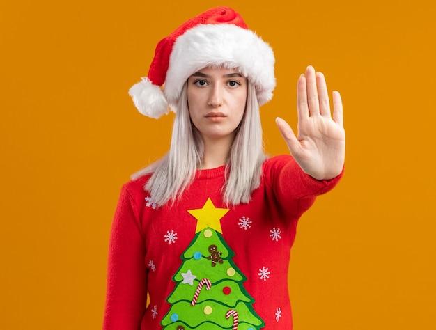 Jovem loira com suéter de natal e chapéu de papai noel com cara séria fazendo gesto de parada com a mão em pé sobre a parede laranja