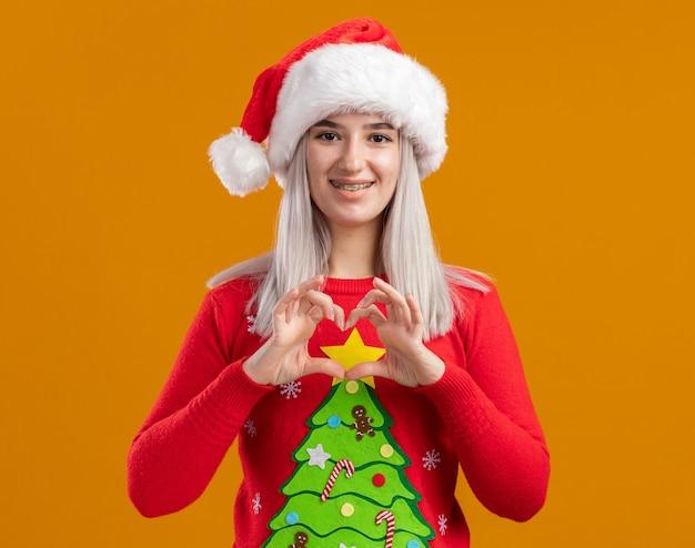Jovem loira com suéter de natal e chapéu de papai noel olhando para a câmera com um sorriso no rosto e fazendo um gesto de coração com os dedos em pé sobre um fundo laranja