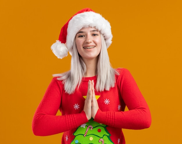 Jovem loira com suéter de natal e chapéu de papai noel olhando para a câmera segurando as palmas das mãos juntas como um gesto namaste feliz e positivo em pé sobre um fundo laranja