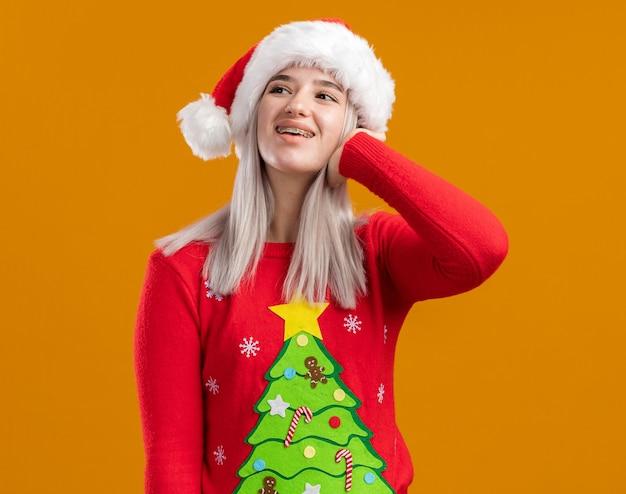 Jovem loira com suéter de natal e chapéu de papai noel olhando para o lado com uma cara feliz em pé sobre um fundo laranja