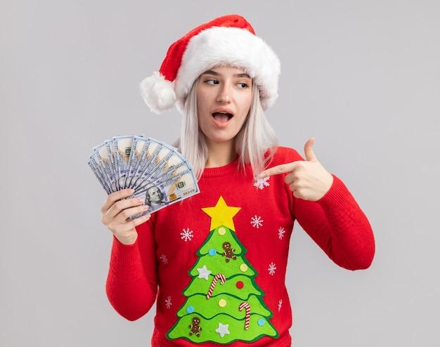 Jovem loira com suéter de natal e chapéu de papai noel segurando dinheiro, apontando com o dedo indicador para dinheiro, feliz e surpresa