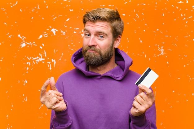Jovem loira com um cartão de crédito, vestindo um capuz roxo contra parede laranja danificada