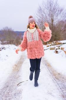 Jovem loira com um casaco de pele rosa, botas de inverno e um chapéu roxo na neve. caminhando em um caminho cheio de neve, estilo de vida